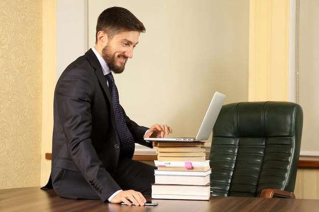 Homme d'affaires prospère assis à la table de bureau et travaillant avec un ordinateur portable