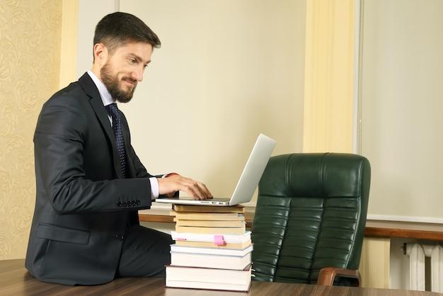 Homme d'affaires prospère au bureau travaillant avec un ordinateur portable