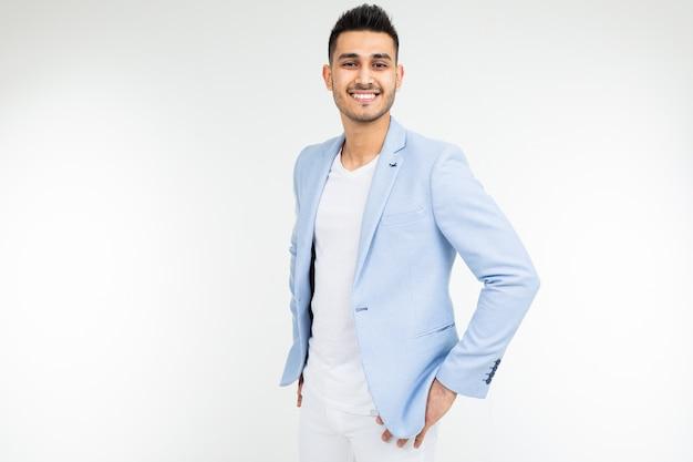 Homme d'affaires prospère dans une veste bleue posant sur un blanc avec espace de copie