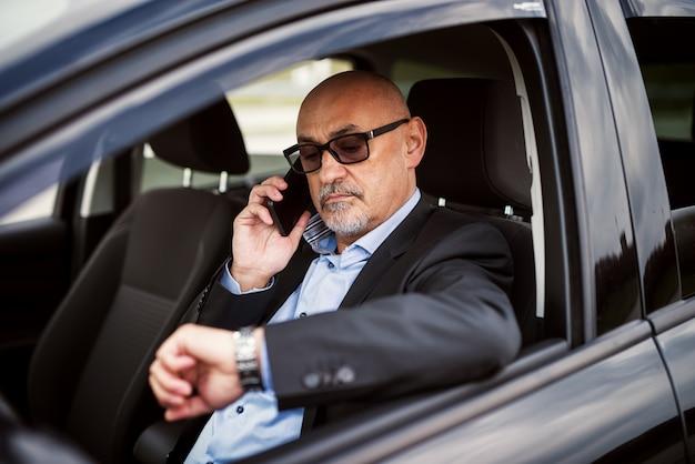 Homme D'affaires Prospère Mature Vérifie L'heure Tout En Parlant Au Téléphone à L'intérieur De Sa Voiture. Photo Premium