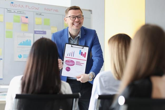 Homme d'affaires prospère montrant des graphiques sur des documents lors d'une conférence devant des étudiants