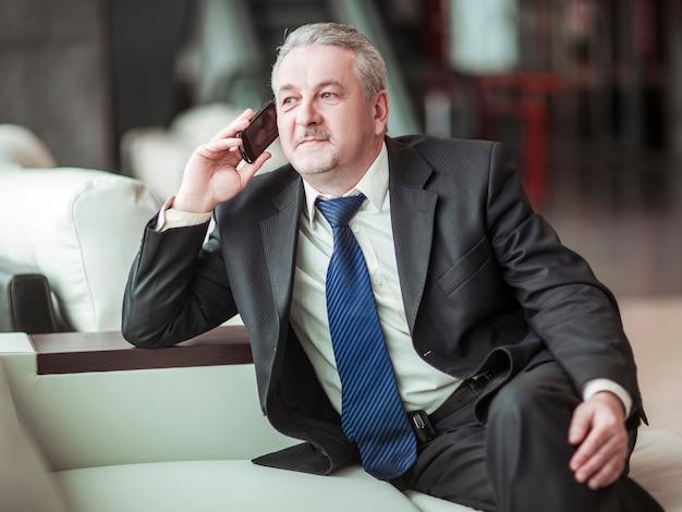 Homme d'affaires prospère parlant sur son smartphone assis sur un canapé au bureau