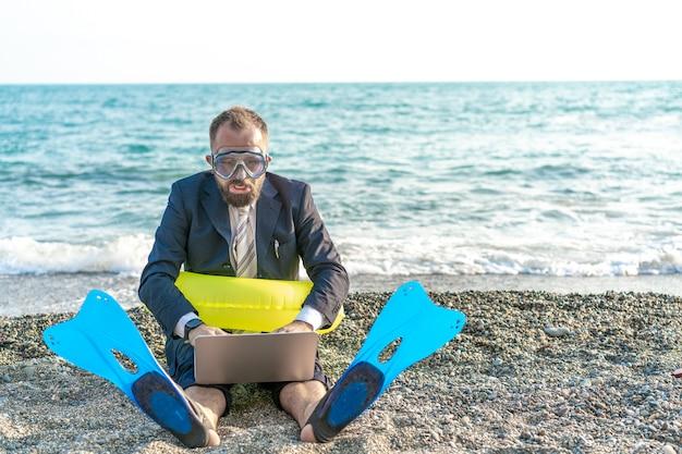 Homme d'affaires prospère portant des outils de plongée en apnée travaille sur la plage avec un ordinateur portable