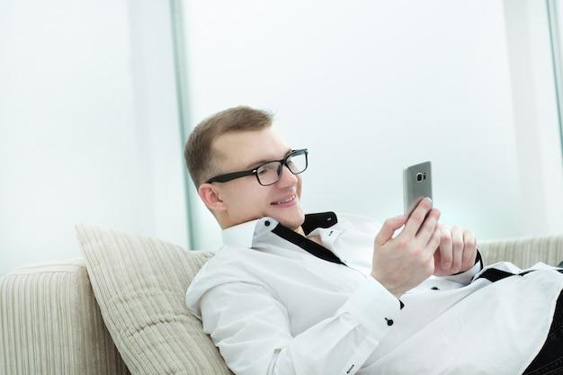 Homme d'affaires prospère en tapant tout en lisant du texte sur son smartphone. les gens et la technologie