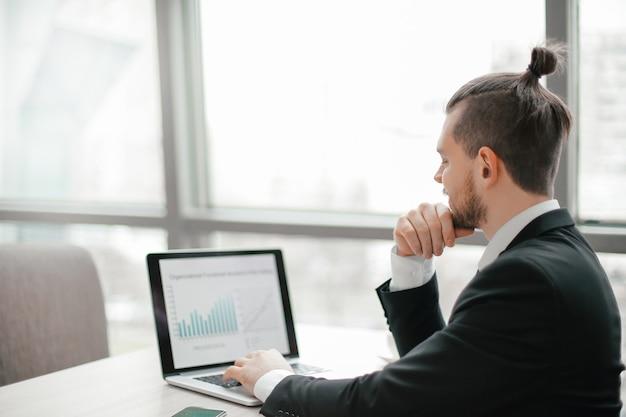 Homme d'affaires prospère travaillant avec des graphiques financiers sur l'ordinateur portable.