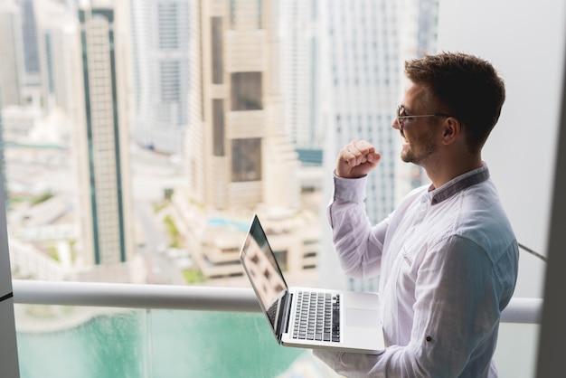 Homme d'affaires prospère avec vue panoramique sur le bureau de la ville. ordinateur portable de travail poing vers le haut.