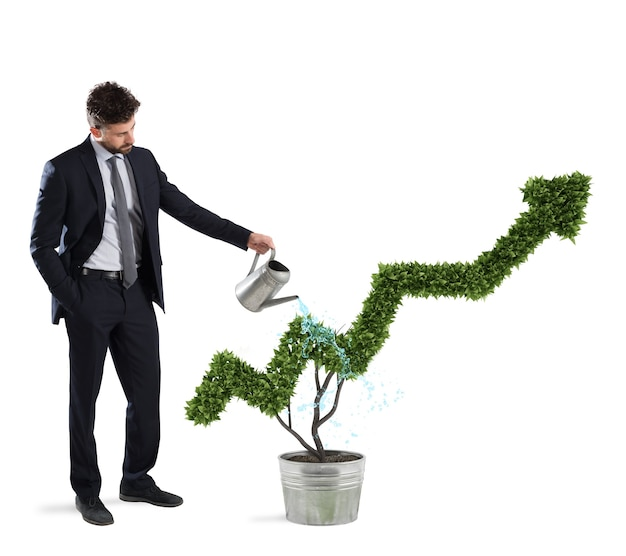 Homme d'affaires qui arrose une plante avec une forme de flèche