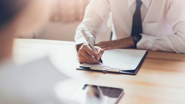 Un homme d'affaires qui écrit un formulaire soumet un cv à son employeur pour examiner sa candidature.