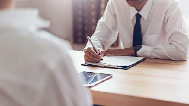 Un homme d'affaires qui rédige un formulaire soumet un cv à son employeur pour examiner sa candidature.