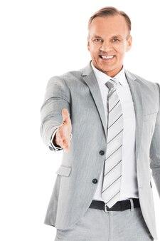 Homme d'affaires qui tend la main pour trembler et sourire, isolé sur un mur blanc