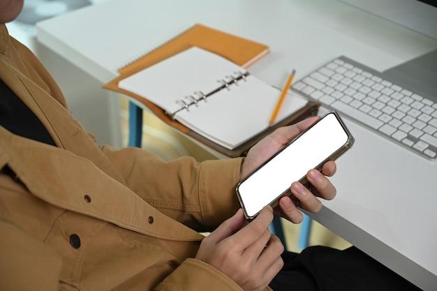 Homme d'affaires recadré assis au bureau et utilisant un téléphone intelligent.
