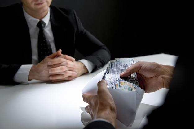Homme d'affaires recevant de l'argent, dollars américains, dans l'enveloppe du partenaire