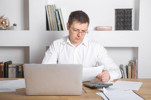 Homme d'affaires recevant des nouvelles négatives, touchant ses lunettes, étant fou, bouleversé et surpris devant un ordinateur portable.