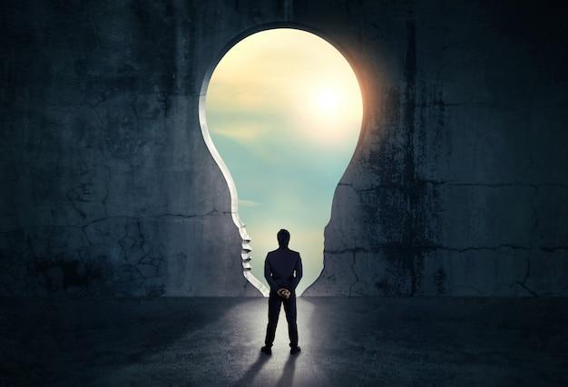 Homme d'affaires à la recherche d'une ouverture abstraite dans le mur