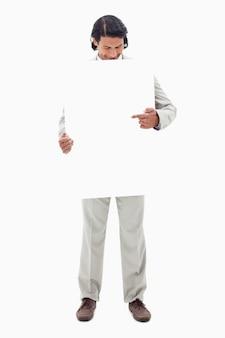Homme d'affaires à la recherche et pointant sur signe vierge dans ses mains