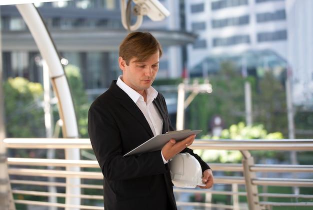 Homme d'affaires à la recherche sur un presse-papiers et tenant un casque