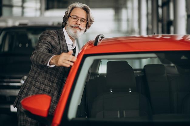 Homme d'affaires à la recherche d'une voiture dans un salon de voiture