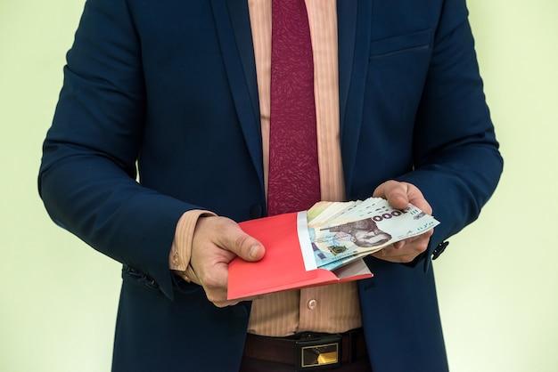 L'homme d'affaires reçoit de l'argent comme pot-de-vin dans une enveloppe