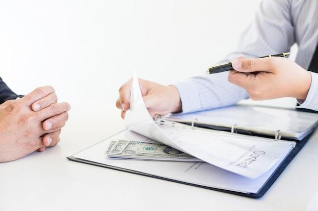 Un homme d'affaires reçoit de l'argent en prenant un pot-de-vin et en signant un contrat de corruption.