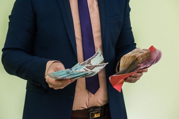 Homme d'affaires reçoit de l'argent sous forme de pot-de-vin dans une enveloppe. un homme donne tout un tas d'argent ukrainien hryvnia dans une enveloppe