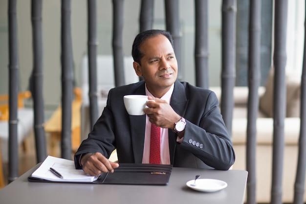 Homme d'affaires réfléchi boire du café au café