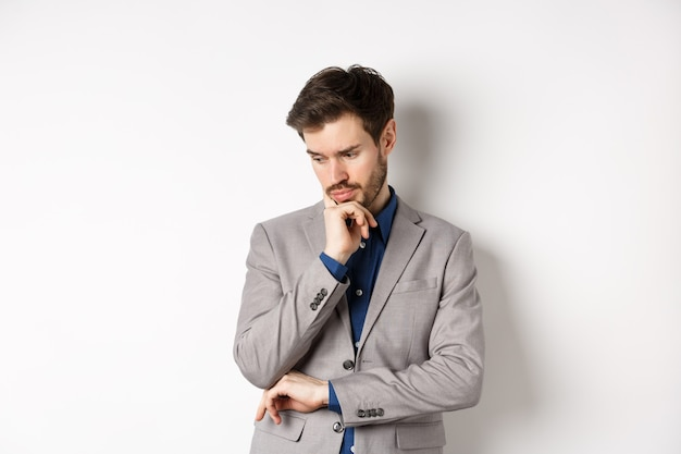 Homme d'affaires réfléchi en costume regardant vers le bas et penser, prendre une décision, debout sur fond blanc.