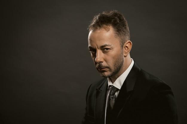 Homme d'affaires réfléchi ou triste sur fond sombre. bel homme mature bien habillé en costume noir et cravate regarde la caméra.