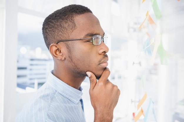 Homme d'affaires réfléchie, lire des notes autocollantes