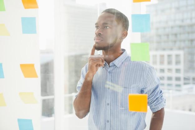 Homme d'affaires réfléchie en regardant les notes autocollantes sur la fenêtre