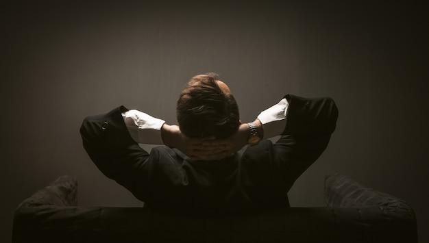 Homme d'affaires réfléchissant à un nouveau projet de démarrage assis sur un canapé. vue arrière de l'homme en costume noir assis sur le canapé