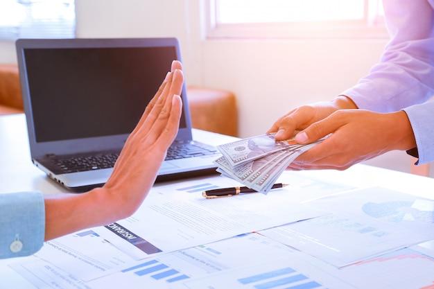 Homme d'affaires refusant de l'argent dans l'enveloppe offerte par un homme