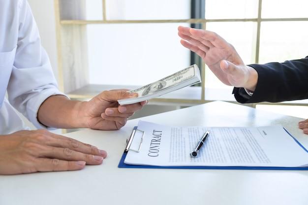 Homme d'affaires refusant de recevoir un pot-de-vin dans l'enveloppe de leur partenaire pour donner du succès au contrat dans une arnaque de corruption, illégale, malhonnête, corruption et corruption