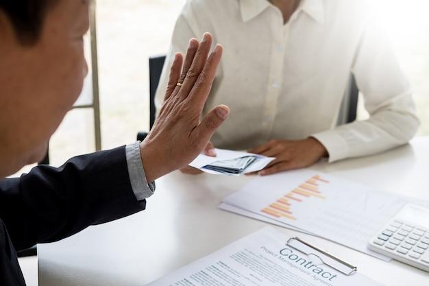 Homme d'affaires refusant ou rejetant de l'argent dans l'enveloppe
