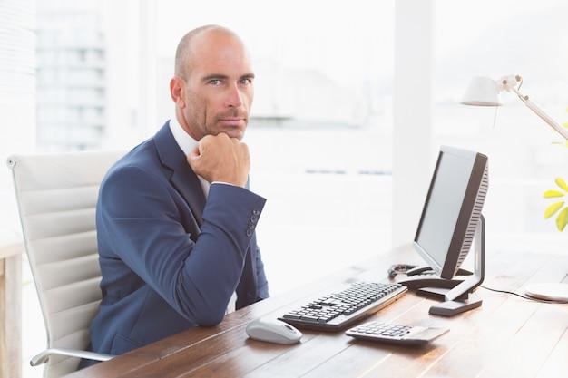 Homme d'affaires en regardant la caméra à son bureau