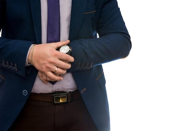 Homme d'affaires regardant l'horloge avant la réunion d'affaires isolé sur un mur blanc