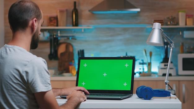 Homme d'affaires regardant un moniteur à écran vert assis à la maison dans la cuisine. indépendant regardant l'affichage du moniteur de bureau avec maquette verte, clé chroma, pendant la nuit en faisant des heures supplémentaires.