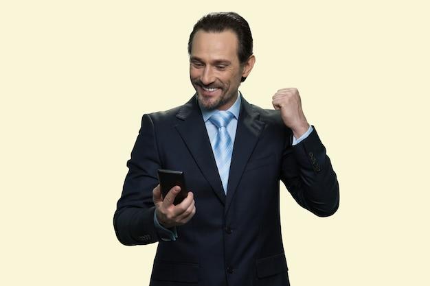 Homme d'affaires regardant sur son téléphone et célébrant le succès. homme d'âge moyen en costume sur fond jaune.