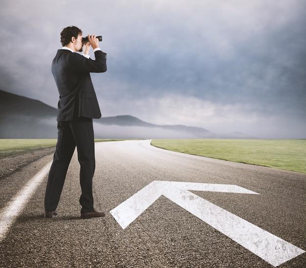 Homme d'affaires regarde l'avenir de l'entreprise avec des jumelles sur la route avec une flèche