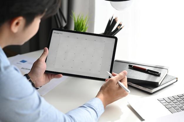 Homme d'affaires regarde le calendrier avec l'ordre du jour quotidien sur tablette.