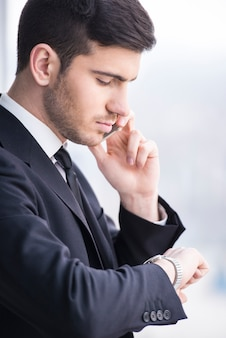 Homme d'affaires regarde sa montre tout en prenant un appel.