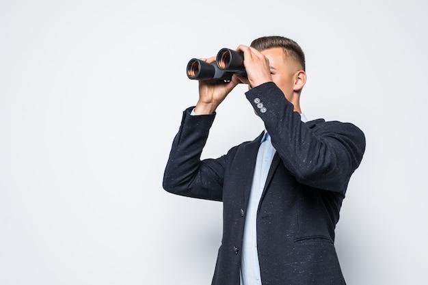 Homme d'affaires regarde à travers une paire de jumelles isolé sur un mur blanc