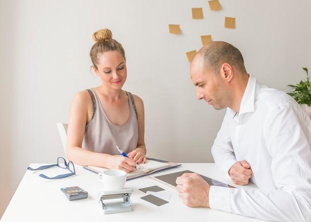 Homme affaires, regarder, femme affaires, écrire, journal, sur, lieu de travail