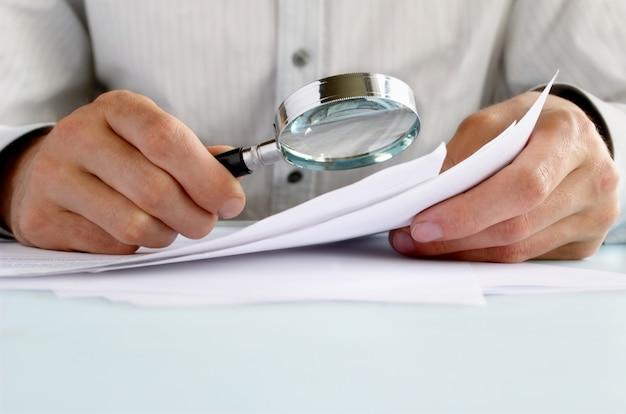 Homme affaires, regarder, par, loupe, documents