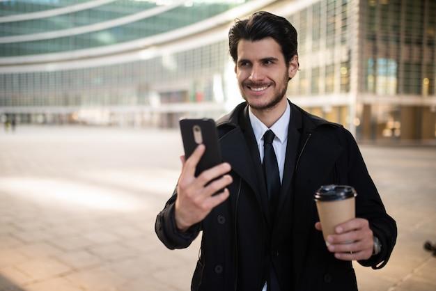 Homme affaires, regarder, smartphone, quoique, boire, café