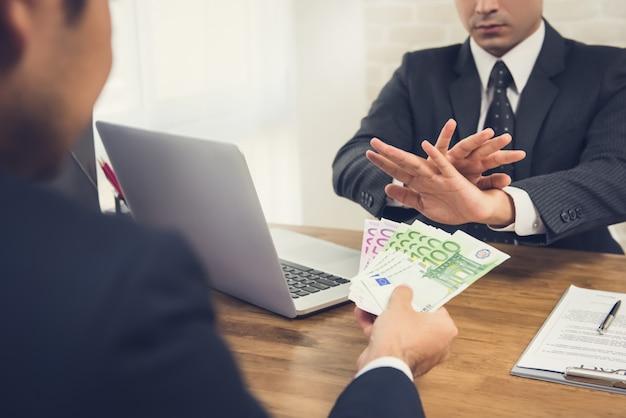 Homme d'affaires rejetant de l'argent, billets en euros, de son partenaire tout en concluant un contrat
