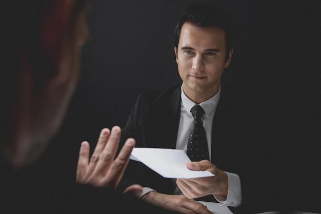 Homme d'affaires rejetant l'argent de la corruption dans une enveloppe blanche offerte par son partenaire