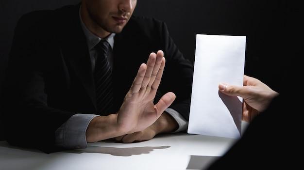Homme d'affaires rejetant de l'argent dans une enveloppe blanche offerte par son partenaire dans l'ombre