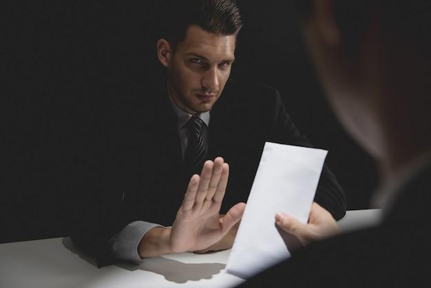 Homme d'affaires rejetant de l'argent dans une enveloppe blanche offerte par son partenaire