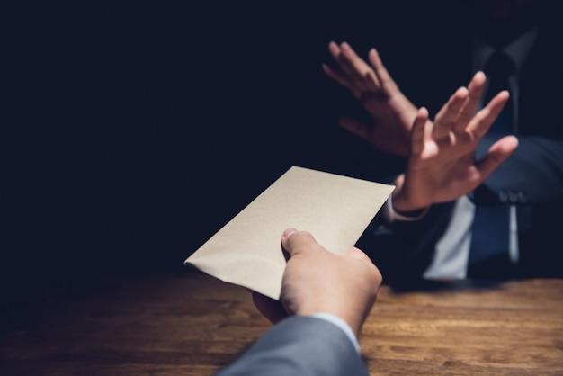 Homme d'affaires rejetant l'argent dans l'enveloppe, concept anti-corruption