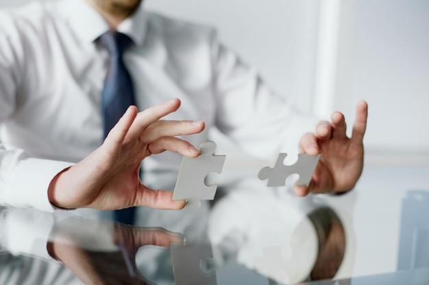 Homme d & # 39; affaires reliant les éléments du puzzle blanc
